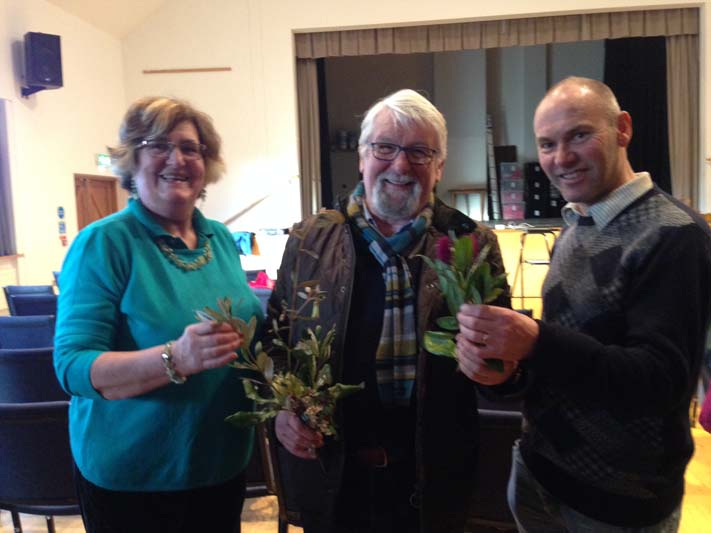 Marion Allen and Victor Henry admiring some of the foliage from Logan brought by the speaker, Richard Baines.