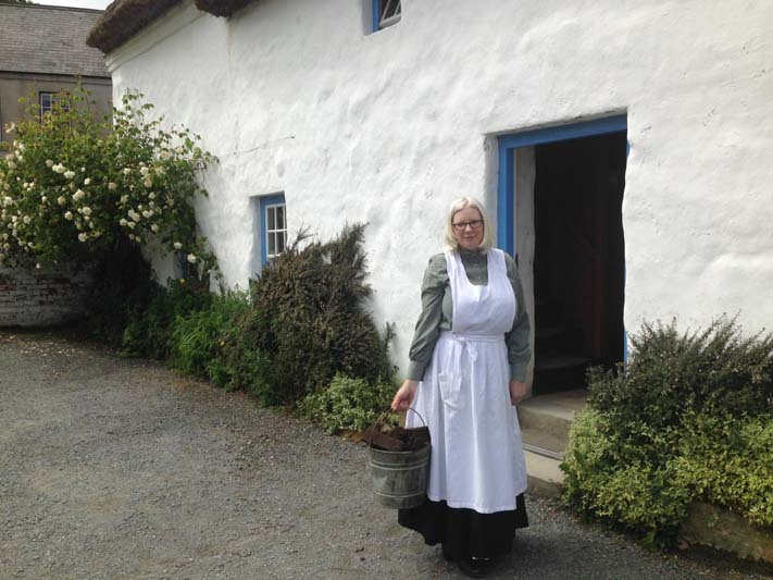 Museum volunteer in period costume bringing in turf for the fire to make soda bread