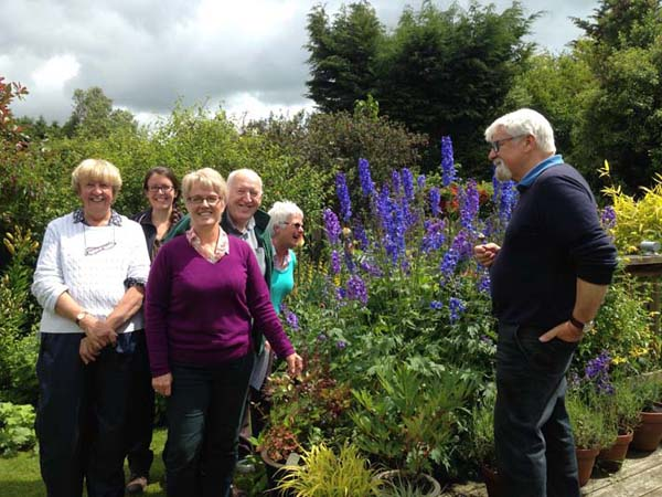 Victor Henry greeting the visitors as all admire the wonderful delphiniums