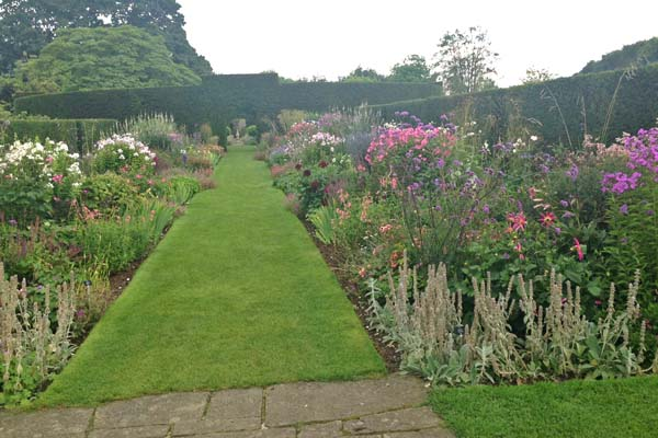 Double herbaceous 'cool' borders. Beyond is the Yew Circle, which surrounds the herb garden.  This circular hedge is one of the oldest features of the garden, dating back to the 1820's.  Barbara Kelso